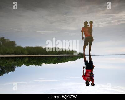 Upside Down Image Of Father Carrying Son Reflecting In Sea At Beach - Stock Photo