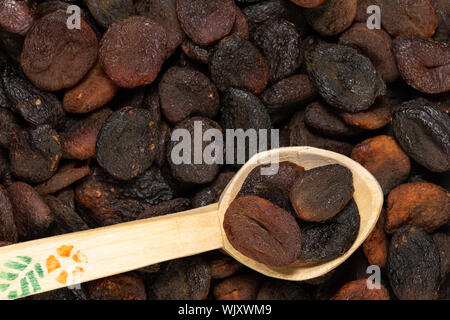 Closeup of dark brown colored dried apricots in a wooden scoop with selective focus. - Stock Photo