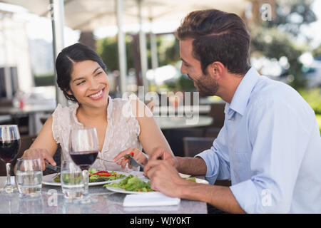 Happy couple on a date having lunch in patio of restaurant - Stock Photo
