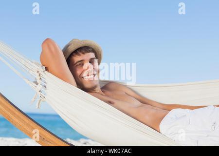 Smiling man wearing straw hat looking - Stock Photo