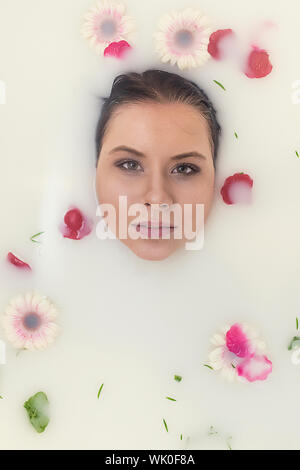 Portrait Of Woman Relaxing In Bathtub With Various Flowers - Stock Photo