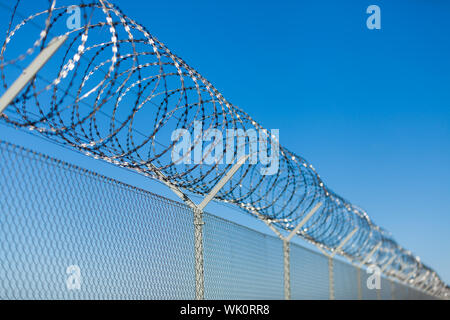 Coiled razor wire with its sharp steel barbs on top of a wire mesh perimeter fence ensuring safety and security, preventing access or the escape of pr - Stock Photo
