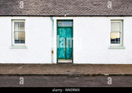Detail of green door and two windows on white wall house - Stock Photo