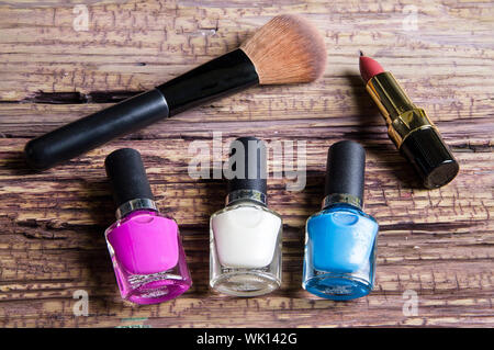 High Angle View Of Nail Polish Bottles With Lipstick And Make-up Brush On Wooden Table - Stock Photo