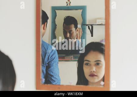 Reflection Of People In Mirror At Home - Stock Photo