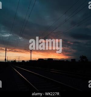 Sunset On Railroad Tracks Against Cloudy Sky - Stock Photo