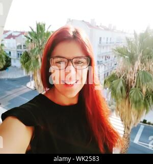 Portrait Of Smiling Woman In Sunglasses Outdoors In City - Stock Photo