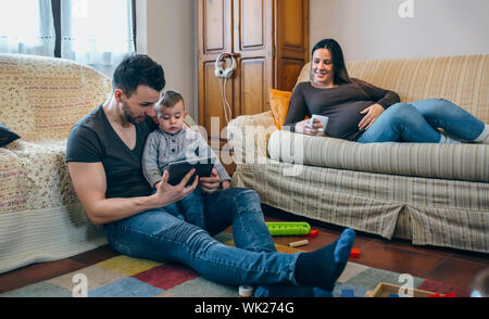 Mother Looking At Father With Son Using Digital Tablet While Sitting In Living Room - Stock Photo