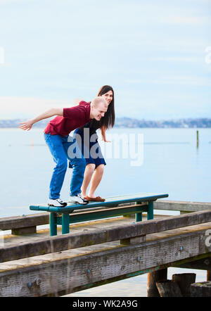 Happy young interracial couple  preparing to jump off  dock over lake, playful - Stock Photo