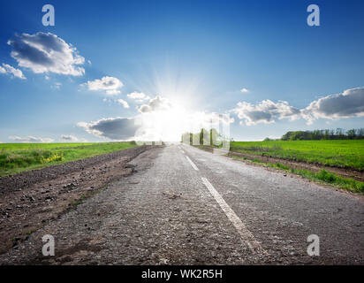 Asphalted highway in the field and sunlight - Stock Photo