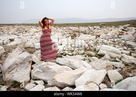 A girl with dark hair stands on white stones in the steppe and looks up. Hands touched the head. Red striped dress. Behind the fog. Copy space. - Stock Photo