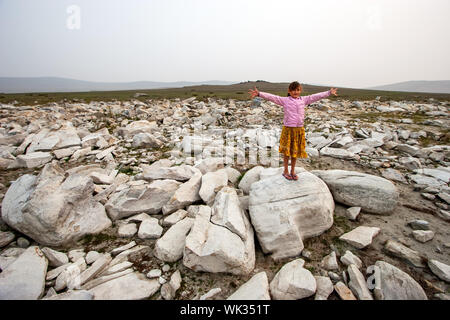 Girl child stands with arms outstretched on a large white stone in the steppe. In a purple jacket and a yellow skirt. Misty sky and hills from behind. - Stock Photo