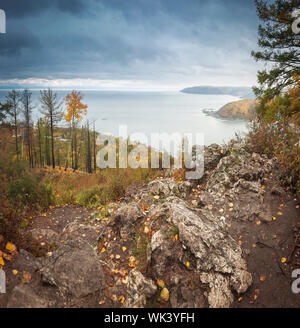sun rises from behind the mountains at sunrise over the lake Baikal - Stock Photo
