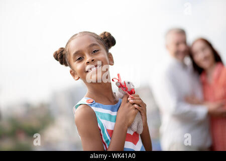 Dark-skinned daughter feeling happy after receiving toy - Stock Photo