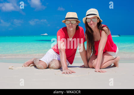 Close up of couple sitting in the heart on tropical beach - Stock Photo