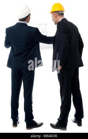Two architects in a suit looking building plan - Stock Photo