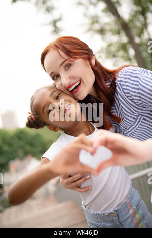 Red-haired woman with bright lips hugging her funny daughter - Stock Photo