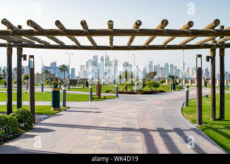 Traditional Wooden Entrance to Grassy City Park by Corniche, with a view of the West Bay Skyline - Doha, Qatar - Stock Photo