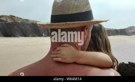 Rear View Of Shirtless Man Wearing Hat Carrying Daughter At Beach Against Sky During Sunny Day - Stock Photo