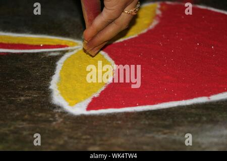 Cropped Hand Of Woman Making Rangoli On Floor - Stock Photo