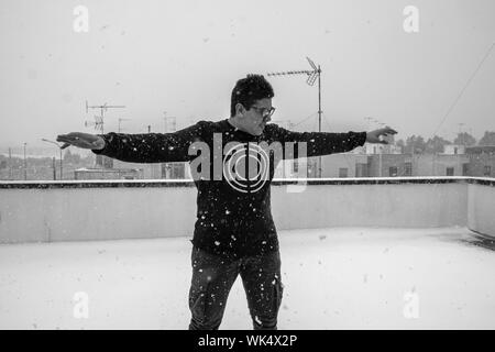 Front View Of Man With Arms Outstretched Standing On Building Terrace During Snowfall - Stock Photo