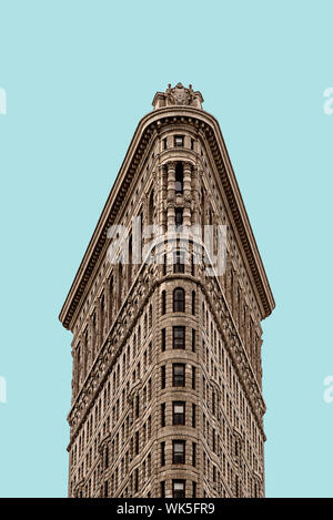 New York City, USA - June 20, 2018: Flatiron Building in Manhattan. Low angle view against flat blue sky. It is one of the worlds most iconic skyscrap - Stock Photo