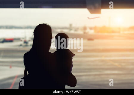 Silhouette of mother holding on hands little toddler boy with window of airport on background. Departure and arrival. Single mother with child - Stock Photo