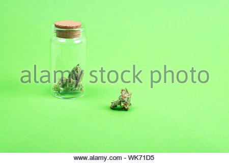 Dried medical marijuana buds in a small open glass jar and scattered aside on green background. Alternative treatment. Medical cannabis. Copy space. - Stock Photo