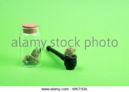 Dried medical marijuana buds in a small open glass jar with wooden pipe on green background. Alternative treatment. Medical cannabis. Place for text. - Stock Photo