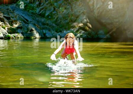 Cheerful Girl Playing In Lake At Big Basin Redwoods State Park - Stock Photo