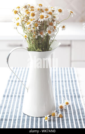 Bouquet of simple chamomiles in vintage pitcher on kitchen table - Stock Photo