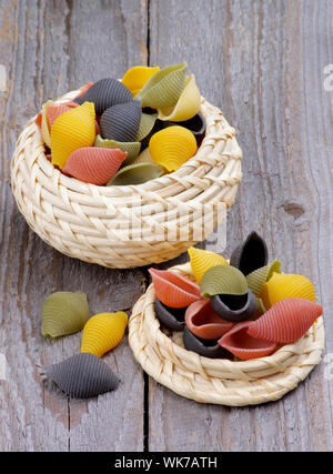 Colorful Conchiglie Pasta in Wicker Bowls isolated on Rustic Wooden background - Stock Photo