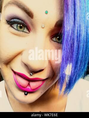 Close-up Portrait Of Young Female Hipster Sticking Out Tongue - Stock Photo