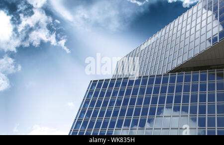 Modern office building detail with glass surface against blue sky and clouds. - Stock Photo