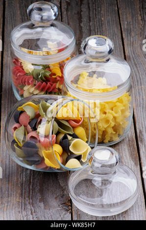 Arrangement of Colorful Conchiglie Pasta, Ballerine Pasta and Rotini Pasta in Glass Jars isolated on Wooden background - Stock Photo