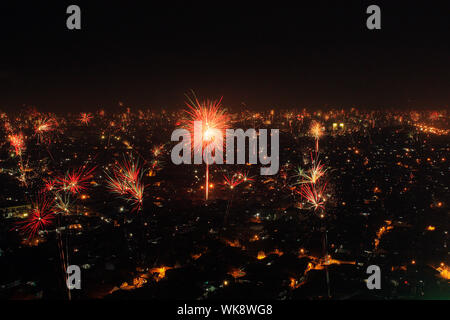 Firework Display Over City During New Year Eve - Stock Photo