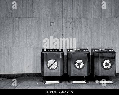 Recycle Bins In Row Against Wall - Stock Photo