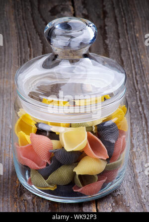 Colorful Conchiglie Pasta in Glass Jar isolated Wooden background - Stock Photo