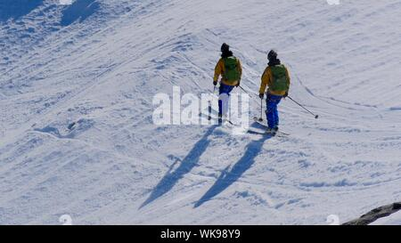 Rear View People Skiing On Snow Covered Field By Rocky Mountain Against Sky - Stock Photo