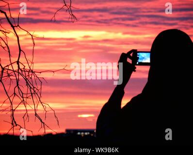 Silhouette Of Woman Photographing At Sunset - Stock Photo