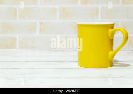 Close-up Of Yellow Mug On Table - Stock Photo