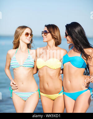 summer holidays and vacation concept - girls in bikinis walking on the beach - Stock Photo