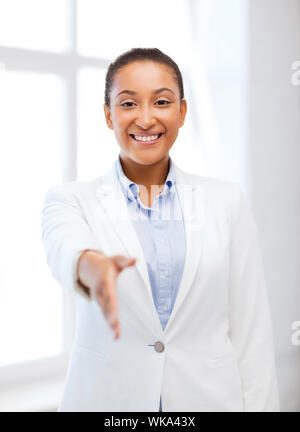 business and education concept - african businesswoman with an open hand ready for handshake - Stock Photo