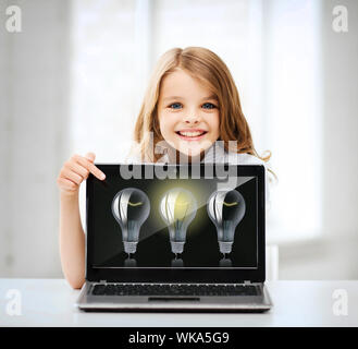 education, school, technology and internet concept - little student girl pointing at laptop pc with light bulbs at school - Stock Photo