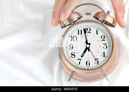 Alarm clock  on a bed with hands of a man holding a clock. - Stock Photo