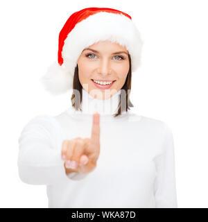 woman in santa helper hat pressing vitrual button - Stock Photo