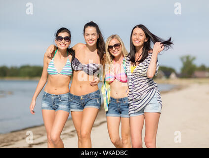girls in bikinis walking on the beach - Stock Photo