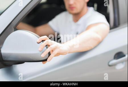 man ajusting rear view mirror - Stock Photo