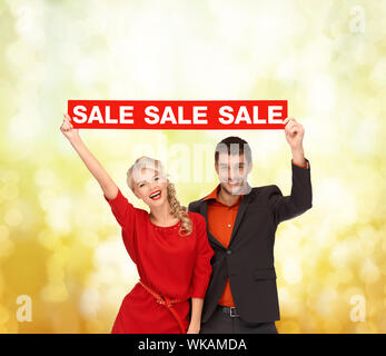 woman and man with red sale sign - Stock Photo