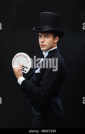magician showing trick with playing cards - Stock Photo